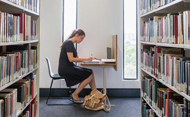 Image of a student studying in the stacks of Fisher library